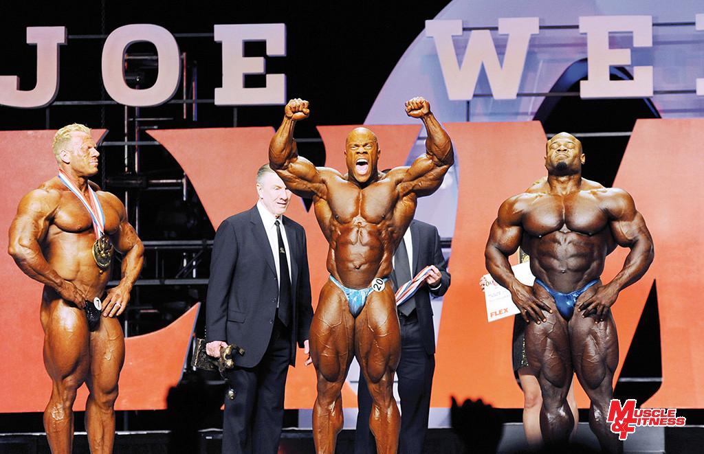 Prvý okamžik po vyhlásení poradia na Mr. Olympia 2013. Uúprostred v návale nadšenia víťaz Phil Heath, vľavo bronzový Dennis Wolf, vpravo neúspešný dobyvateľ trónu Kai Greene.