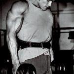 Krčení ramen s jednoručkami. Cvičí Arnold.